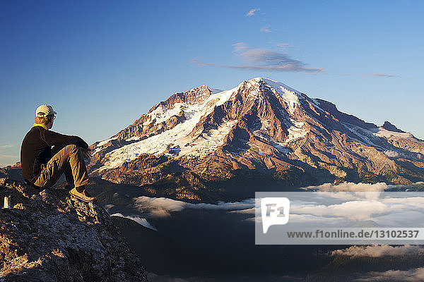 Seitenansicht eines auf einem Berg sitzenden Mannes vor klarem Himmel