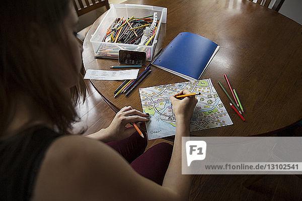 Teenage girl drawing map sitting at table