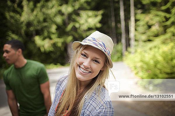 Porträt einer glücklichen Frau mit Freundin auf der Landstraße stehend