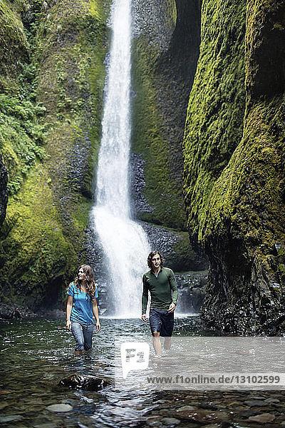Paar steht im Strom gegen Wasserfall