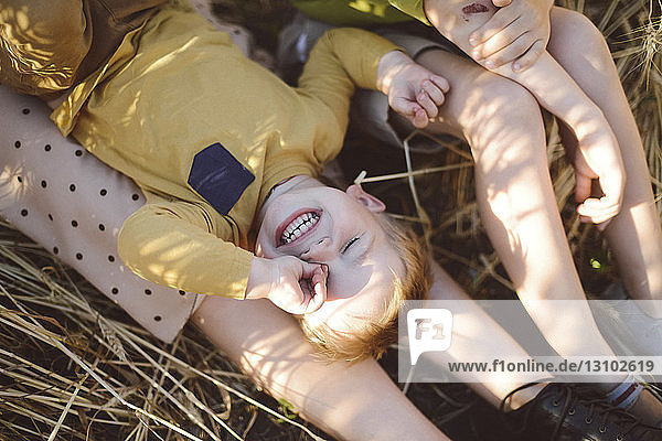 Boy rubbing eye while lying on mother's legs by brother on field