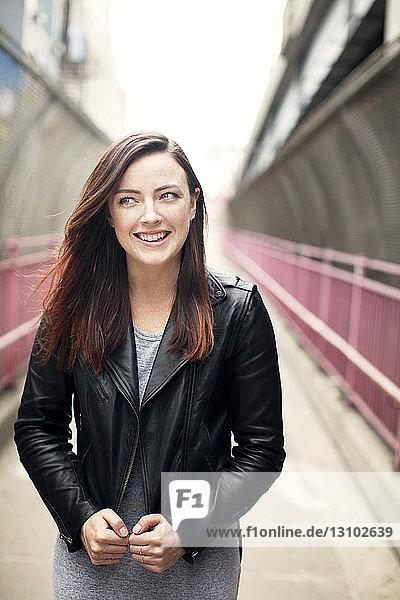 Porträt einer lächelnden Frau  die auf dem Gehweg steht