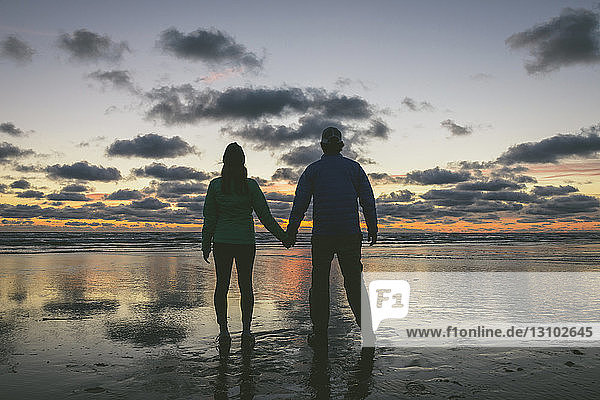 Rear view of couple holding hands while standing at Long Beach against cloudy sky