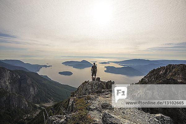 Unbekümmerter Wanderer mit Rucksack mit Blick auf die Aussicht  während er auf dem Berg gegen den Himmel steht