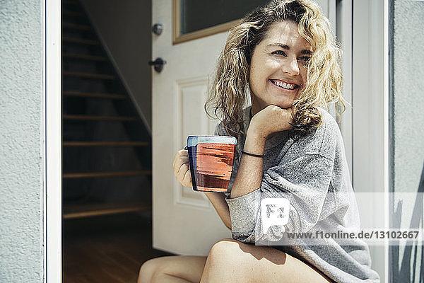 Glückliche Frau hält Kaffeetasse in der Hand  während sie an der Tür sitzt
