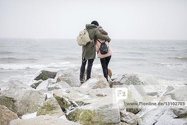 Rückansicht eines Paares mit Rucksäcken  das sich umarmt  während es auf Felsen am Strand am Meer vor klarem Himmel steht