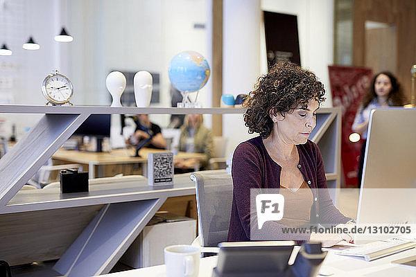 Ältere Geschäftsfrau benutzt Desktop-Computer  während sie im Kreativbüro am Schreibtisch sitzt