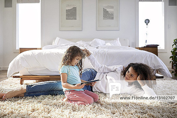 Mutter sieht Tochter am Tablet-Computer an  während sie auf dem Teppich im Schlafzimmer liegt