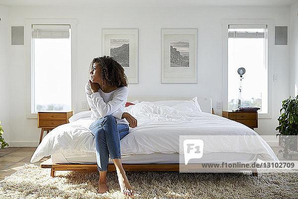 Nachdenkliche Frau schaut weg  während sie zu Hause auf dem Bett sitzt