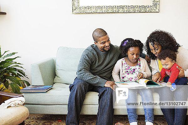 Familie schaut ins Bilderbuch  während sie auf dem Sofa sitzt