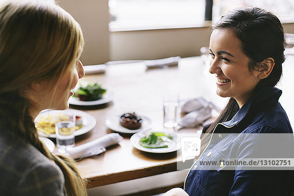 High angle view of happy female friends talking while sitting at table in restaurant
