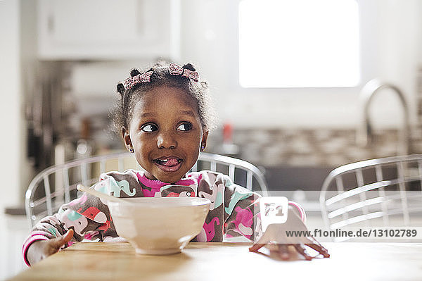 Cute girl making face while having breakfast in kitchen