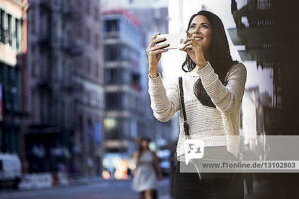 Happy woman photographing through smart phone in city