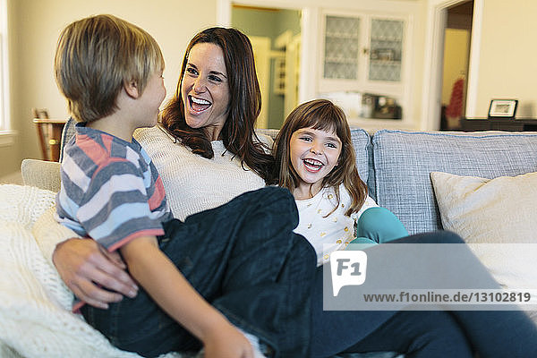 Cheerful mother with children sitting on sofa at home
