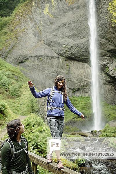 Mann sieht Freundin an  die am Wasserfall auf einem Geländer läuft