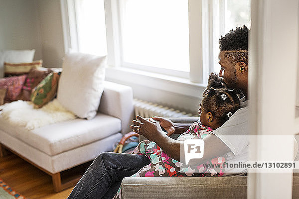 Side view of father using tablet computer with children in living room