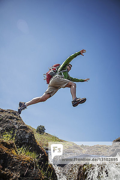 Low angle view of male hiker jumping over stream