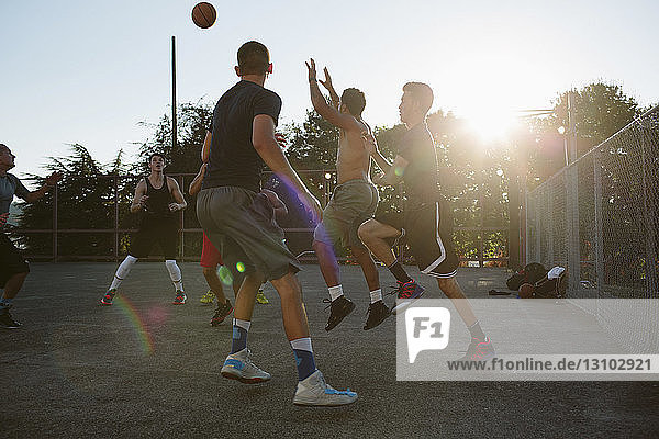 Basketball players playing in court