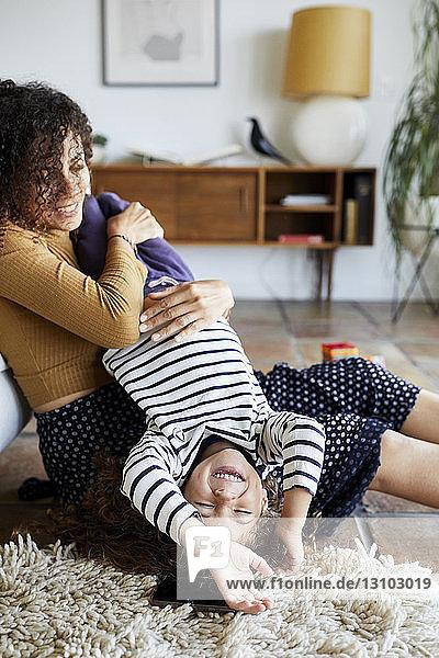 Glückliche Mutter hält Tochter kopfüber  während sie zu Hause auf dem Boden sitzt