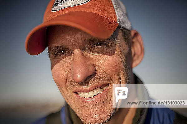 Close-up of smiling man against clear sky