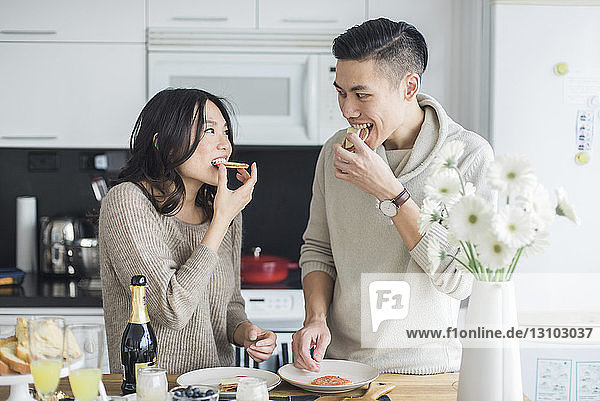 Couple eating breakfast while standing at table in kitchen