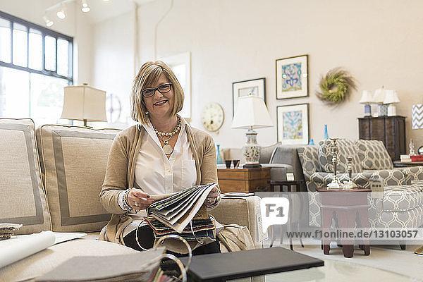 Porträt einer Besitzerin  die auf einem Sofa in einem Möbelgeschäft sitzt