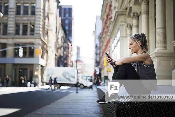 Sportlerin benutzt Mobiltelefon  während sie in der Stadt auf dem Bürgersteig sitzt