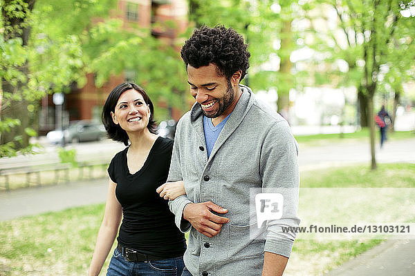 Cheerful multi-ethnic couple walking in park