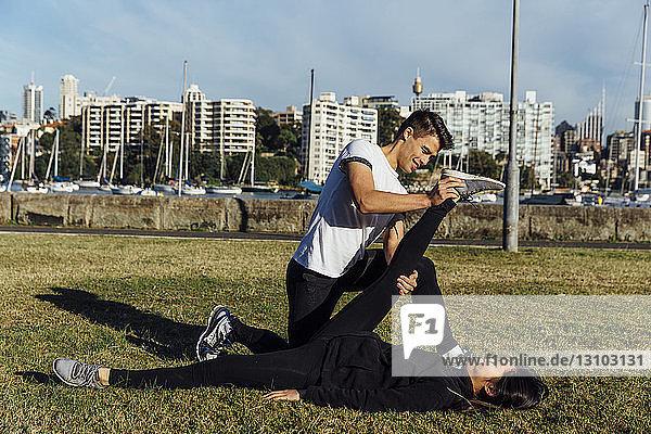 Freundin hilft ihrer Freundin beim Beinstrecken gegen das Stadtbild