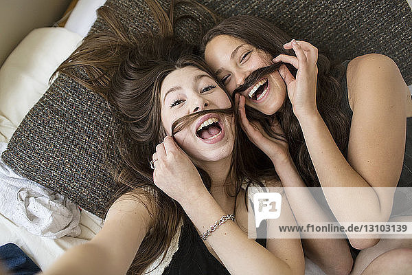 Overhead portrait of female friends making artificial mustache with hair