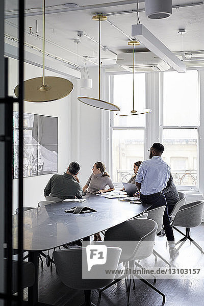 Colleagues looking at television while sitting in conference room at creative office