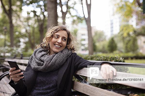 Frau benutzt Mobiltelefon  während sie im Park auf einer Bank sitzt