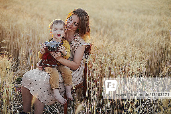 Portrait of cheerful son with camera sitting on mother's laps amidst wheat field
