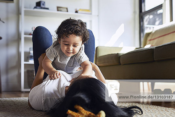 Mother playing with son while lying on carpet at home