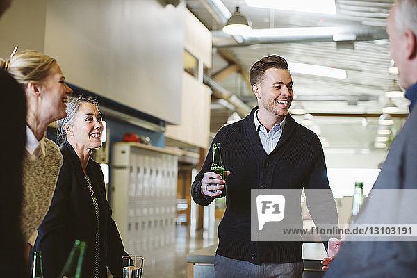Geschäftsleute unterhalten sich bei Getränken im Büro