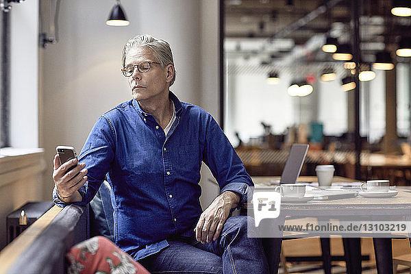 Leitender Geschäftsmann schaut auf Smartphone  während er in der Büro-Cafeteria sitzt