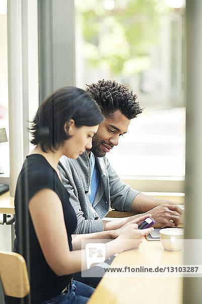 Multi-ethnisches Paar benutzt Smartphone im Café