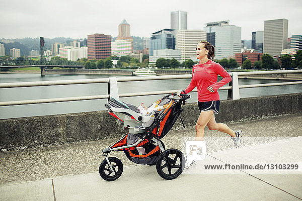 Woman jogging with baby stroller on footbridge by river in city