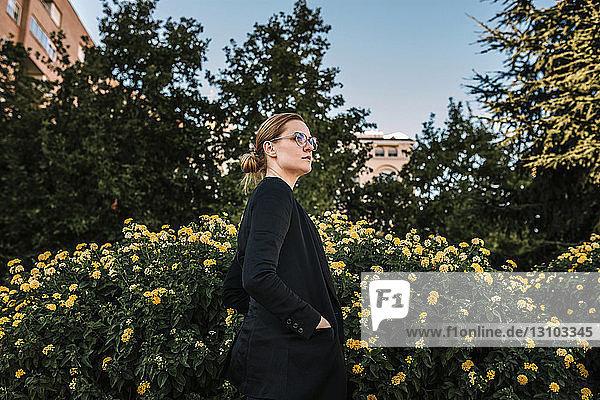 Frau mit Hand in der Tasche steht im Park vor blühenden Pflanzen