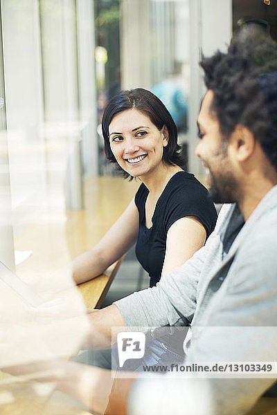 Happy woman sitting with man in cafe seen through glass window