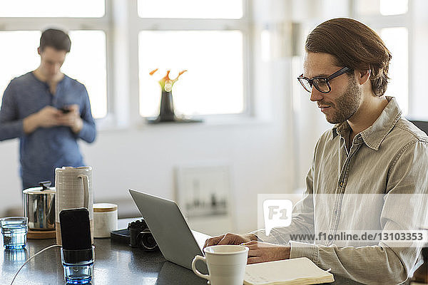 Man using laptop computer at home with boyfriend in background