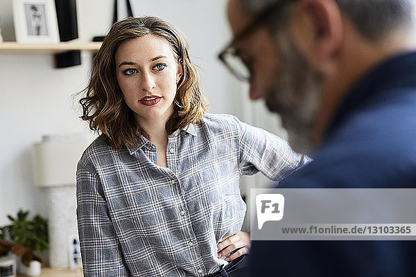 Businessman discussing with female colleague in creative office