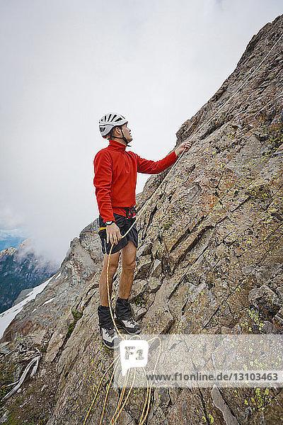 Wanderer in voller Länge mit Seil beim Klettern in Felsformationen gegen Wolken