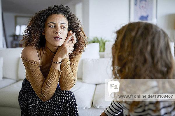 Mutter spricht mit Tochter  während sie zu Hause sitzt