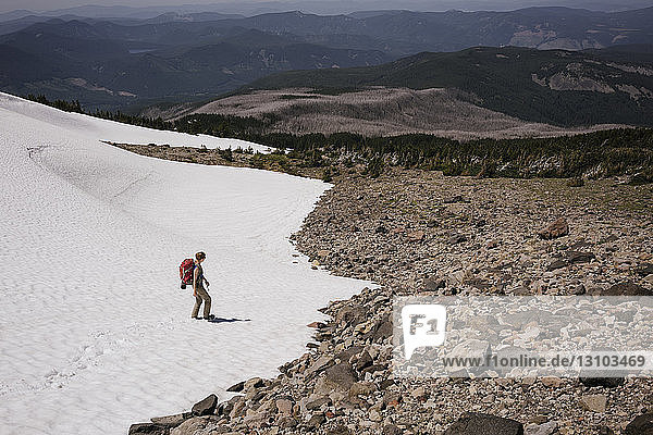 Hochwinkelaufnahme einer Frau auf einem schneebedeckten Berg während eines sonnigen Tages