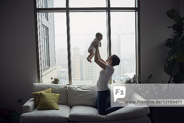 Side view of happy mother lifting son while kneeling on sofa by window at home