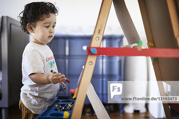 Cute baby boy holding crayon while standing by canvas at home
