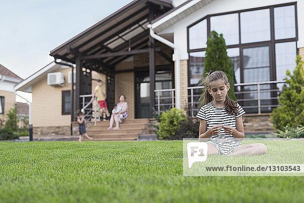 Girl sitting in grass in backyard