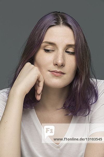 Portrait of a young woman with dyed hair and looking down against gray background