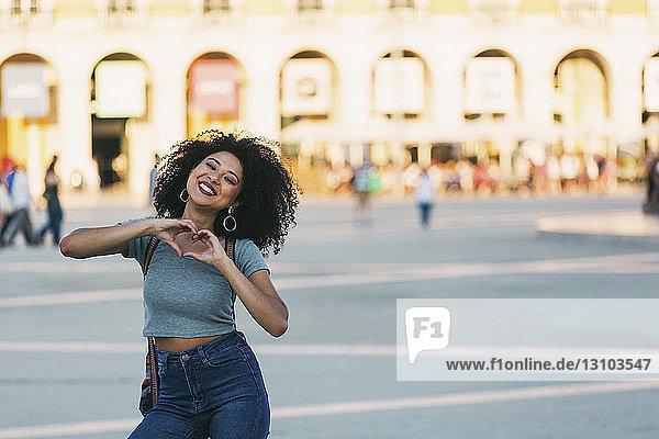Portrait enthusiastic young woman forming heart-shape with hands in Praca do Comercio  Lisbon